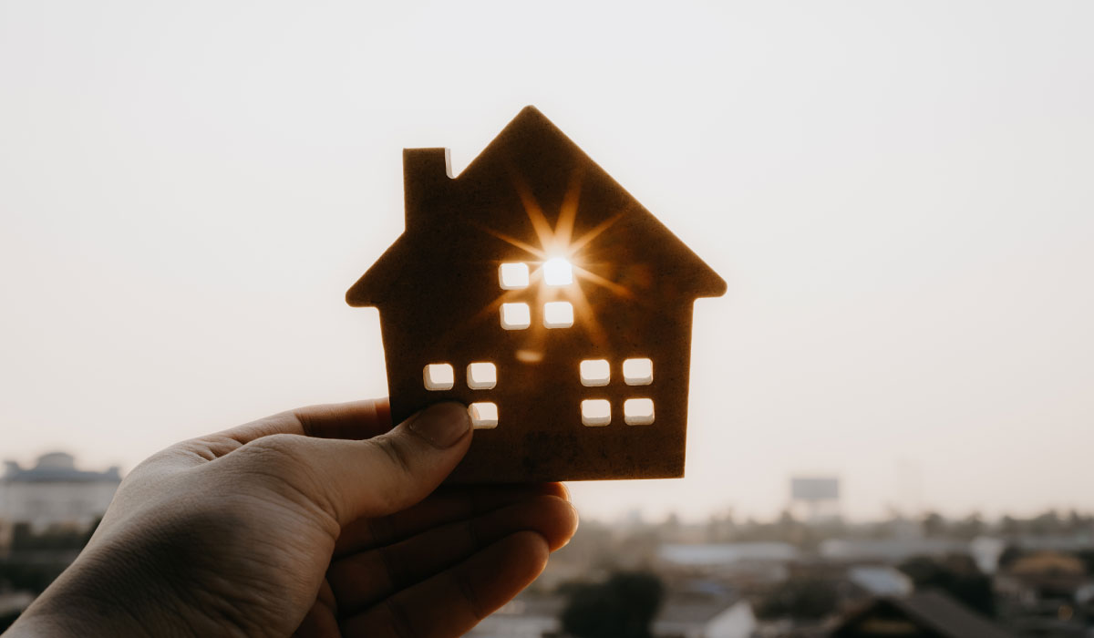 Person holding a cutout of a miniature house with sunlight coming through