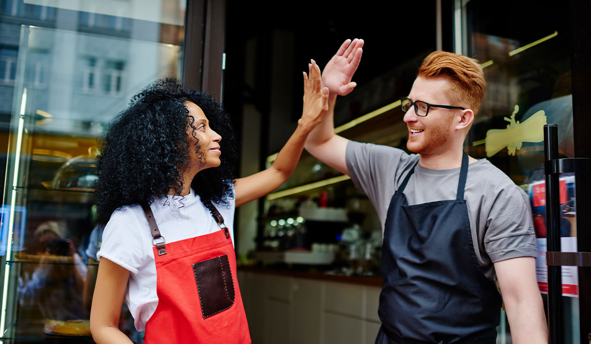 African American woman and Caucasian male waiters high five each other