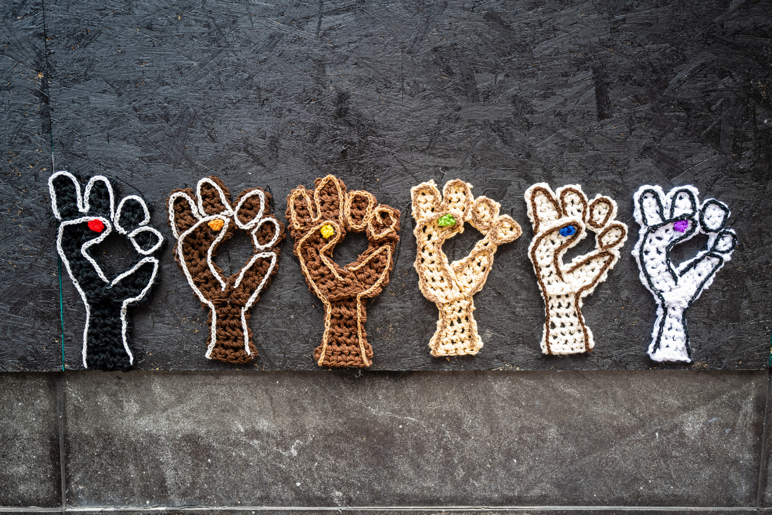 Fists in different skin colors raised in solidarity